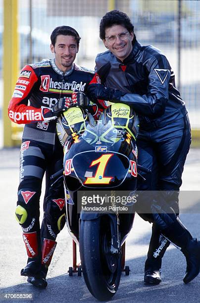 'Max Biaggi and Fabrizio Frizzi in biker suits pose near the Aprilia motorbike with the number 1 on the front with this bike the previous year Biaggi...
