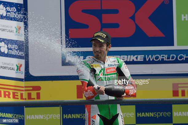 Max Biaggi of Italy and Aprilia Alitalia Racing celebrates on the podium with champagne after winning the Superbike World Championship round two race...