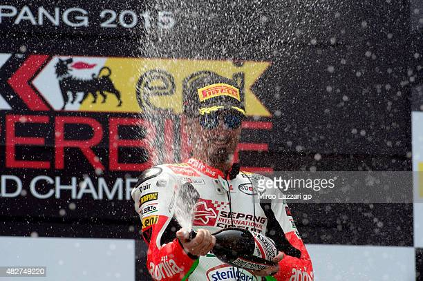 Max Biaggi of Italy and APRILIA RACING TEAM RED DEVILS celebrates the third place with champagne on the podium at the end of the Race 1 during the...