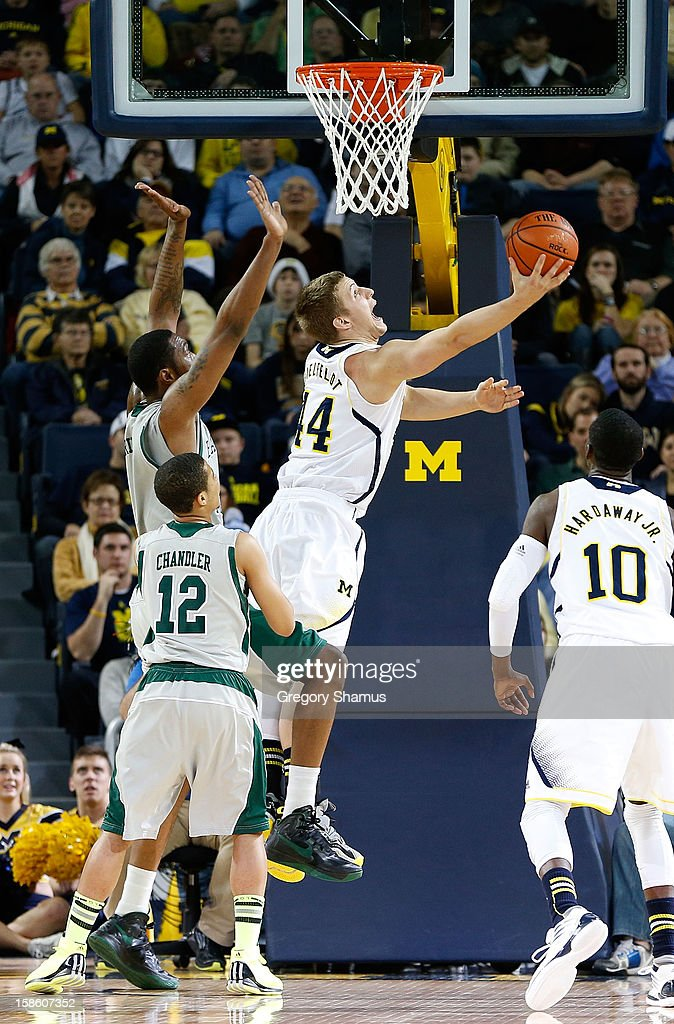 Max Bielfeldt #44 of the Michigan Wolverines gets a second half shot off behind Antoine Chandler #12 of the Eastern Michigan Eagles at Crisler Center on December 20, 2012 in Ann Arbor, Michigan.