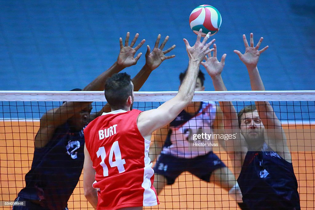 Max Burt of Canada spikes the ball against Gregory Petty and Kristopher Johnson of United States during a match between USA and Canada as part of Men's Panamerican Volleybal Cup at Gimnasio Ol'mpico Juan de la Barrera on May 24, 2016 in Mexico City, Mexico.