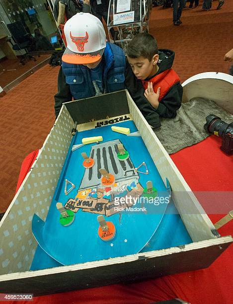 Max Ciancamerla watches as brother Matteo works the manual flippers of a pinball game called Urban Poor The game is part of a project last year with...