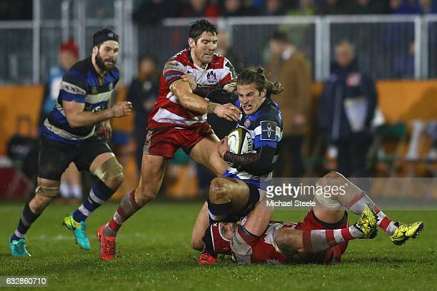 Max Clark of Bath is tackled by Sione Kalamafoni and James Hook of Gloucester during the Anglo Welsh Cup match between Bath Rugby and Gloucester...