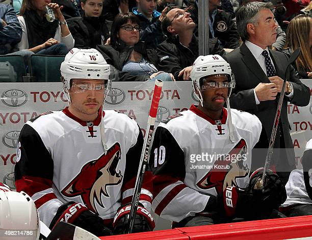 Max Domi and Anthony Duclair of the Arizona Coyotes look on from the bench prior to puck drop against the Winnipeg Jets at the MTS Centre on November...