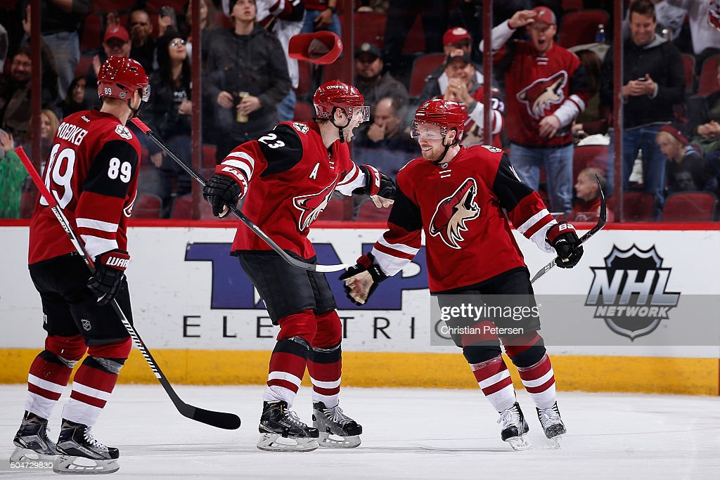 Max Domi #16 of the Arizona Coyotes celebrates with Oliver Ekman-Larsson #23 and Mikkel Boedker #89 after Domi scored a hat trick goal against the Edmonton Oilers during the third period of the NHL game at Gila River Arena on January 12, 2016 in Glendale, Arizona. The Coyotes defeated the Oilers 4-3.