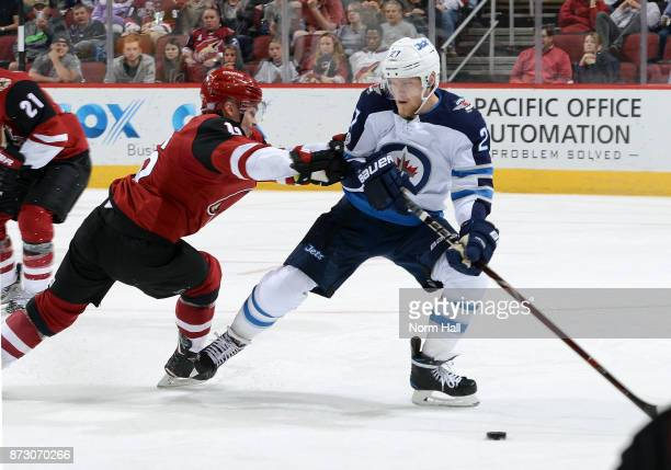 Max Domi of the Arizona Coyotes checks Nikolaj Ehlers of the Winnipeg Jets off the puck during the first period at Gila River Arena on November 11...