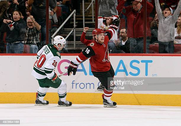 Max Domi of the Arizona Coyotes skates past Ryan Suter of the Minnesota Wild as he celebrates his second period goal at Gila River Arena on October...