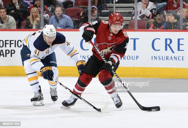 Max Domi of the Arizona Coyotes skates with the puck as Justin Falk of the Buffalo Sabres defends during the third period at Gila River Arena on...