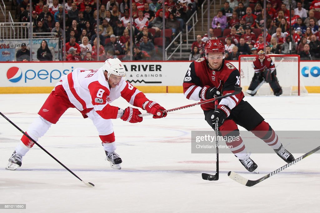 Max Domi #16 of the Arizona Coyotes skates with the puck past Justin Abdelkader #8 of the Detroit Red Wings during the third period of the NHL game at Gila River Arena on October 12, 2017 in Glendale, Arizona. The Red Wings defeated the Coyotes 4-2.
