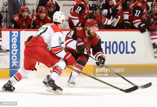 Max Domi of the Arizona Coyotes skates with the puck while being defended by Brett Pesce of the Carolina Hurricanes during the second period at Gila...