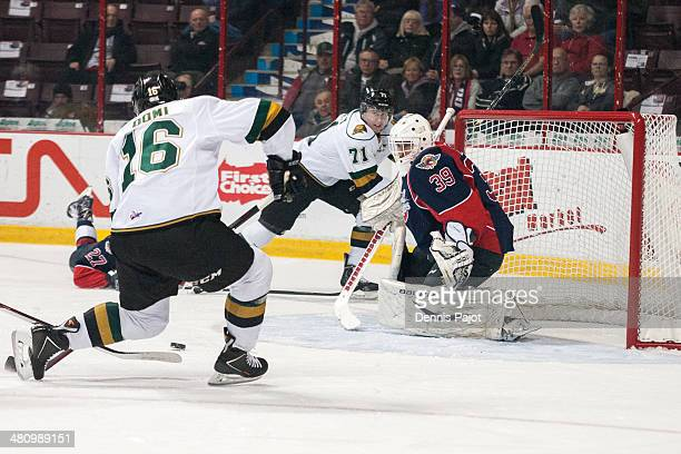 Max Domi of the London Knights moves the puck against Alex Fotinos of the Windsor Spitfires in Game 4 of their OHL QuarterFinal series on March 27...