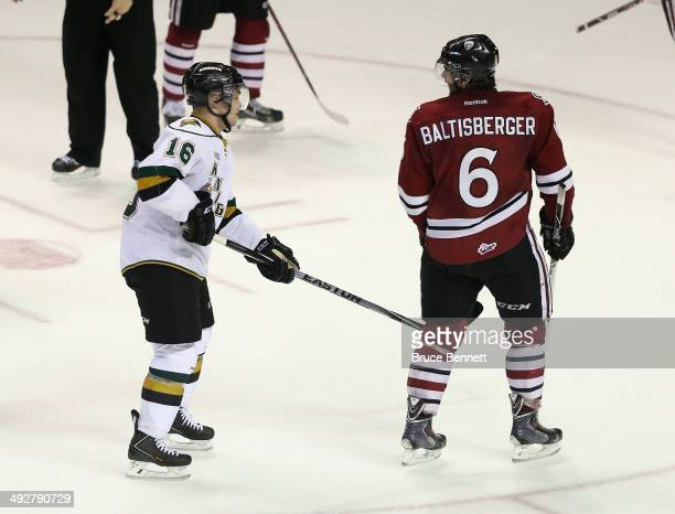 Max Domi of the London Knights takes a two minute penalty for slashing at the 20 minute mark of the third period against Phil Baltisberger of the...