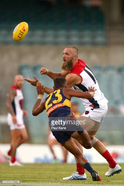 Max Gawn of the Demons handballs against Lewis Jetta of the Eagles during the JLT Community Series AFL match between the West Coast Eagles and the...