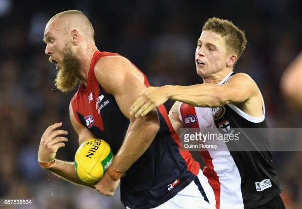 Max Gawn of the Demons handballs whilst being tackled by Jack Billings of the Saints during the round one AFL match between the St Kilda Saints and...
