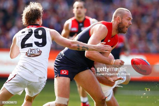 Max Gawn of the Demons handpasses the ball whilst being tackled during the round 21 AFL match between the Melbourne Demons and the St Kilda Saints at...