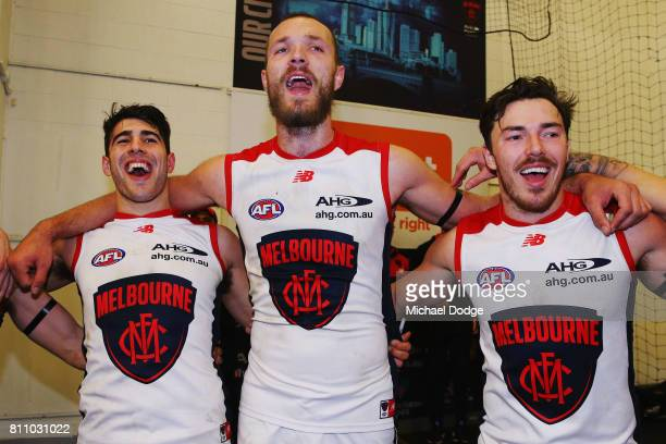 Max Gawn of the Demons hugs Christian Petracca and Michael Hibberd as they sing the club song after winning during the round 16 AFL match between the...