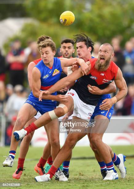 Max Gawn of the Demons kicks whilst being tackled by Jackson Macrae and Tom Boyd of the Bulldogs during the 2017 JLT Community Series match between...
