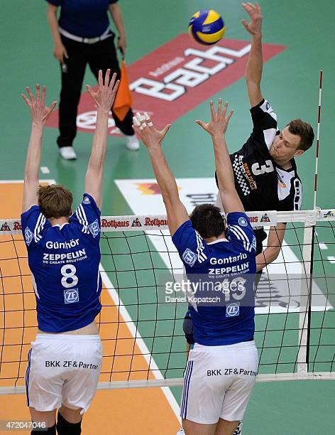 Max Guenthoer of Friedrichshafen tries to block with team mate Adrian Gontariu against Robert Kromm of Berlin during the Volleyball Bundesliga match...