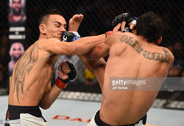Max Holloway of the United States and Charles Oliveira of Brazil trade strikes in their featherweight bout during the UFC event at the SaskTel Centre...