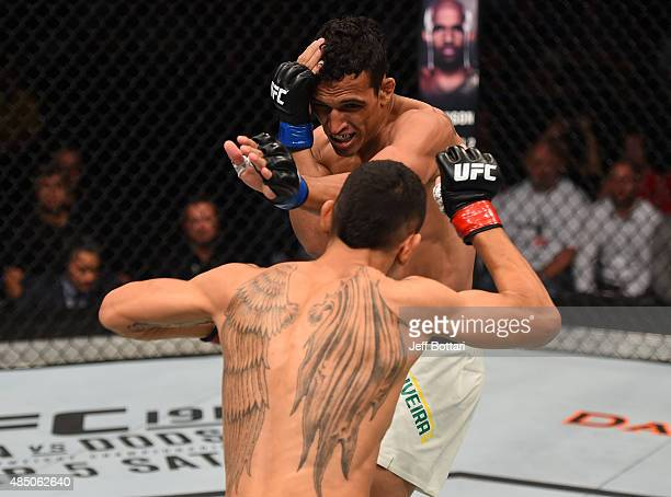 Max Holloway of the United States prepares to deliver a punch against Charles Oliveira of Brazil in their featherweight bout during the UFC event at...