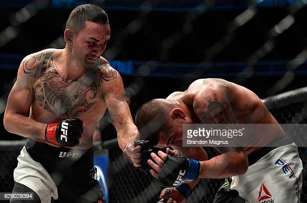 Max Holloway punches Anthony Pettis in their interim UFC featherweight championship bout during the UFC 206 event inside the Air Canada Centre on...