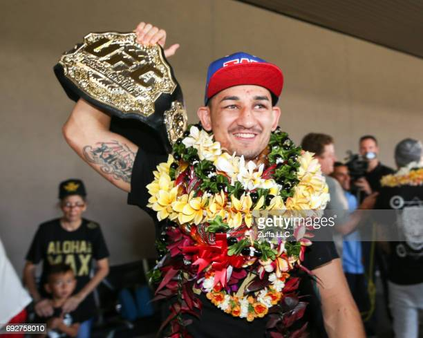 Max Holloway raises his UFC Championship belt as he greets his fans upon his arrival at the Daniel K Inouye International Airport on June 5 2017 in...