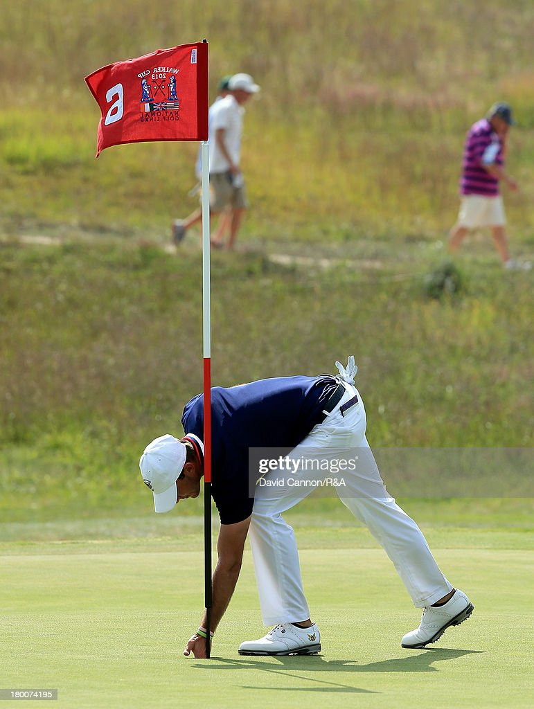 Max Homa of the United States team retrieves his ball after holing his tee shot at the par 3, 6th hole in his match against Kevin Phelan of the Great Britain and Ireland team during the final day afternoon singles matches of the 2013 Walker Cup Match at The National Golf Links of America on September 8, 2013 in Southampton, New York.