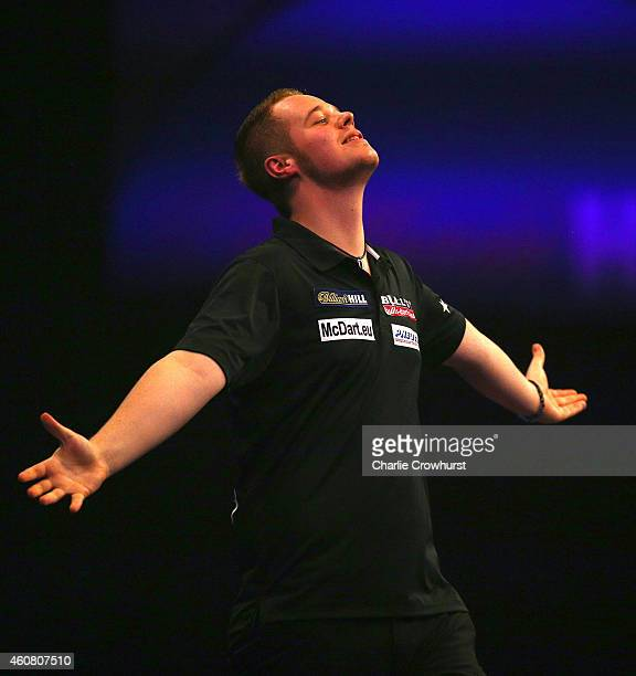 Max Hopp of Germany celebrates winning his first round match against Mervyn King of England during the William Hill PDC World Darts Championships on...