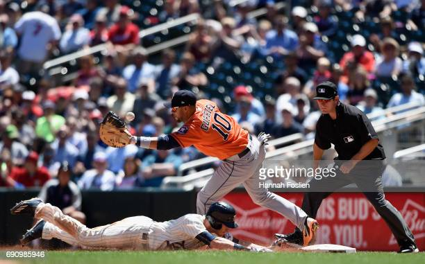 Max Kepler of the Minnesota Twins dives safely back to first base as Yuli Gurriel of the Houston Astros is unable to field the ball and umpire Ben...