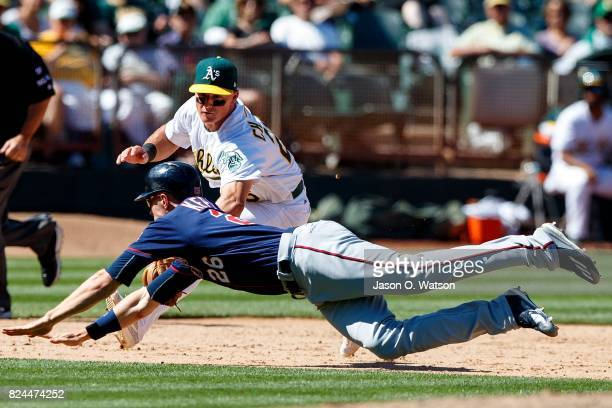 Max Kepler of the Minnesota Twins is tagged out diving into third base by Matt Chapman of the Oakland Athletics during the ninth inning at the...