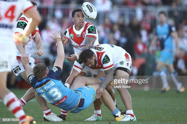 Max King of the Titans tries to offload as he is tackled by Tyson Frizell and Leeson Ah Mau of the Dragons during the round 23 NRL match between the...