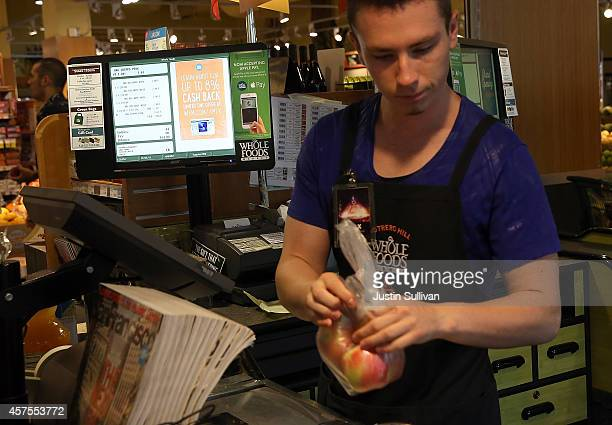 Max Koval rings up customers next to a sign announcing that Whole Foods is accepting Apple Pay at a Whole Foods store on October 20 2014 in San...
