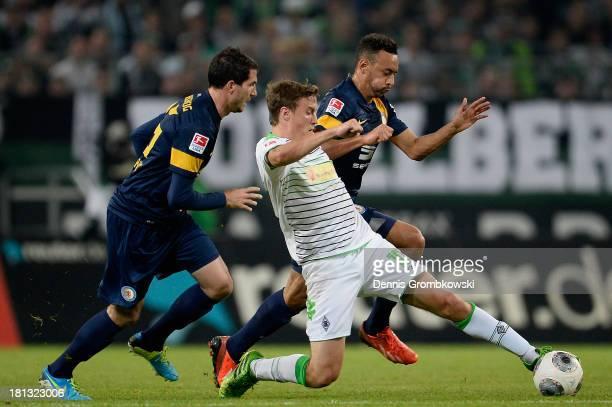 Max Kruse of Borussia Moenchengladbach is challenged by Norman Theuerkauf and Karim Bellarabi of Eintracht Braunschweig during the Bundesliga match...