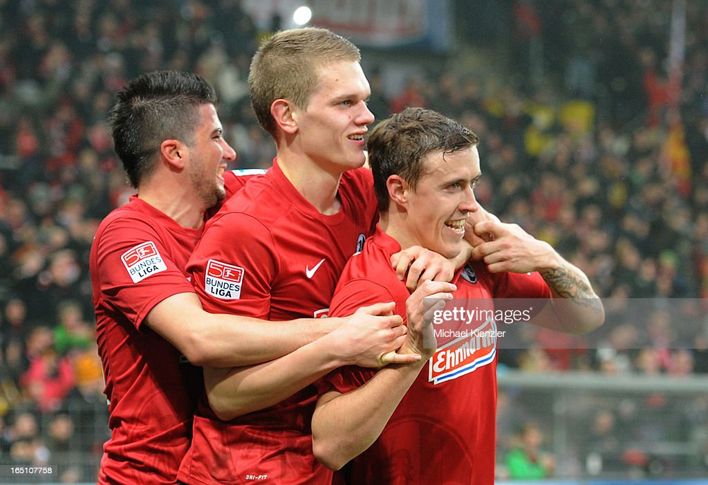Max Kruse of Freiburg (R) celebrates his second goal with Marco Terrazzino (L) and Matthias Ginter (C) during the Bundesliga match between SC Freiburg and VfL Borussia Moenchengladbach at MAGE SOLAR Stadium on March 30, 2013 in Freiburg, Germany.