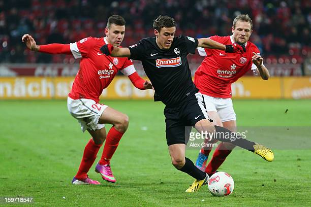 Max Kruse of Freiburg is challenged by Adam Szalai and Bo Svensson of Mainz during the Bundesliga match between 1 FSV Mainz 05 and SC Freiburg at...