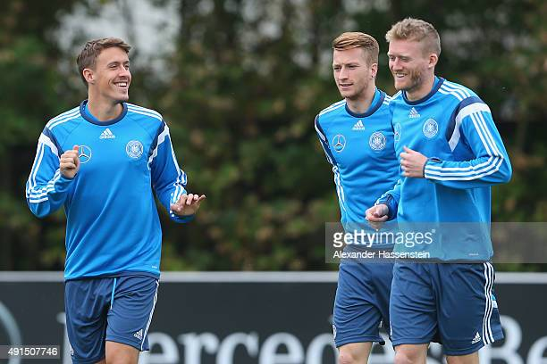 Max Kruse of Germany talks with his team mates Marco Reus and Andre Schuerrle during a training session of the German national football team at...