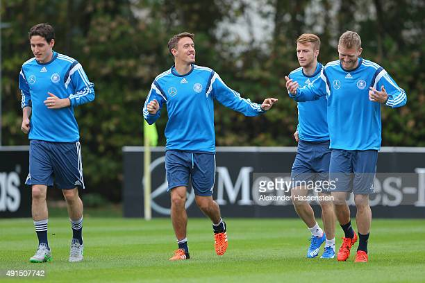 Max Kruse of Germany talks with his team mates Sebastian Rudy Marco Reus and Andre Schuerrle during a training session of the German national...