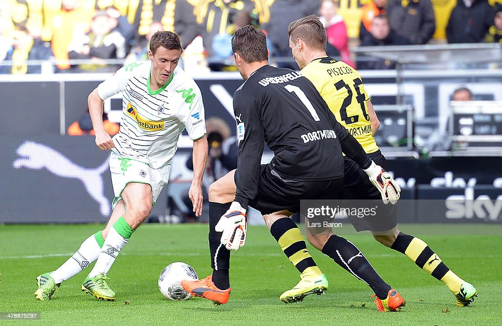 <a gi-track='captionPersonalityLinkClicked' href=/galleries/search?phrase=Max+Kruse&family=editorial&specificpeople=3945507 ng-click='$event.stopPropagation()'>Max Kruse</a> of Moenchengladbach is on his way against goalkeeper <a gi-track='captionPersonalityLinkClicked' href=/galleries/search?phrase=Roman+Weidenfeller&family=editorial&specificpeople=726753 ng-click='$event.stopPropagation()'>Roman Weidenfeller</a> and <a gi-track='captionPersonalityLinkClicked' href=/galleries/search?phrase=Lukasz+Piszczek&family=editorial&specificpeople=4380352 ng-click='$event.stopPropagation()'>Lukasz Piszczek</a> of Dortmund to score his teams second goal during the Bundesliga match between Borussia Dortmund and Borussia Moenchengladbach at Signal Iduna Park on March 15, 2014 in Dortmund, Germany.