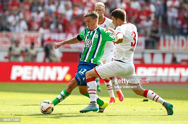 Max Kruse of Wolfsburg challenges Dominique Heintz of Cologne during the Bundesliga match between 1 FC Koeln and VfL Wolfsburg at RheinEnergieStadion...