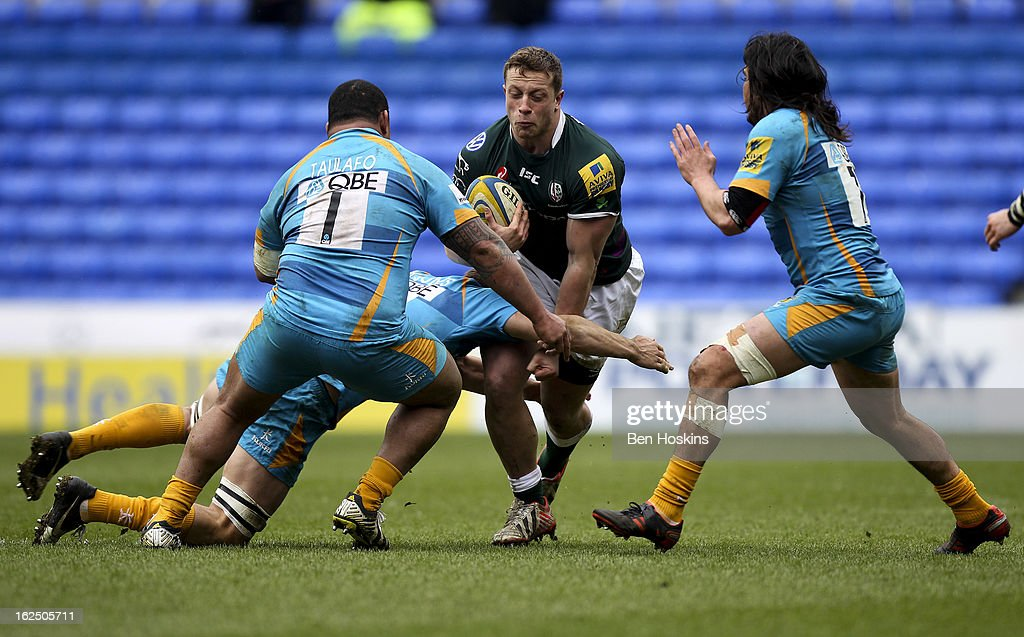 Max Lahiff of London Irish is tackled by Zak Taulafo (L) and Jonathan Poff (R) of Wasps during the Aviva Premiership match between London Irish and London Wasps at the Madejski Stadium on February 24, 2013 in Reading, England.