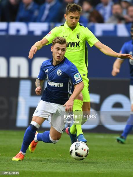 Max Meyer of Schalke and Moritz Leitner of Augsburg compete for the ball during the Bundesliga match between FC Schalke 04 and FC Augsburg at...
