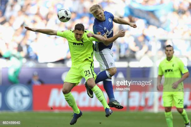 Max Meyer of Schalke battles for the ball with Dominik Kohr of Augsburg during the Bundesliga match between FC Schalke 04 and FC Augsburg at...