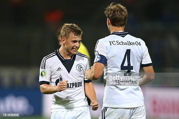 Max Meyer of Schalke celebrates his team's third goal with team mate Benedikt Hoewedes of Schalke during the DFB Cup second round match between...