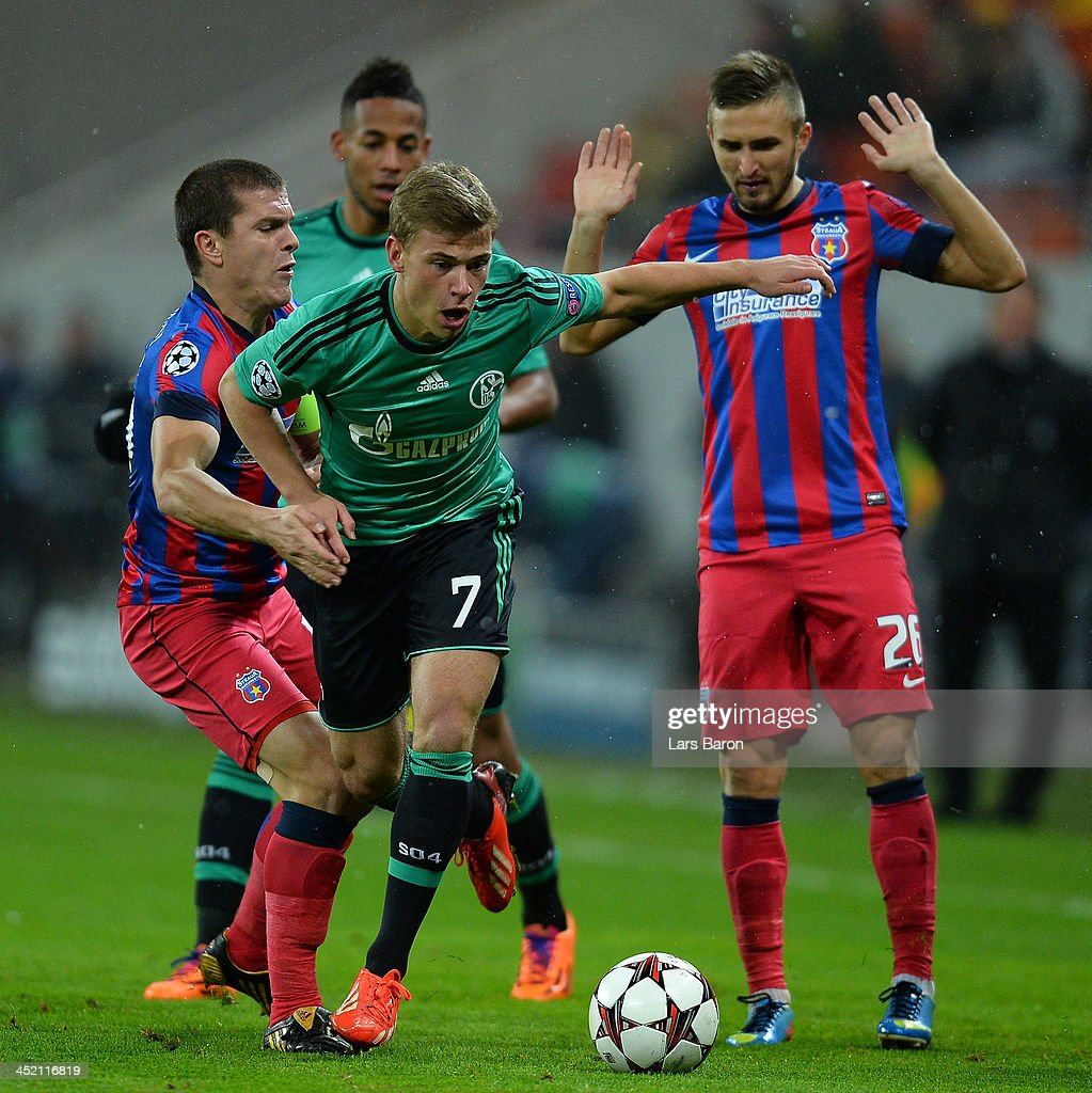 Max Meyer of Schalke is challenged by <a gi-track='captionPersonalityLinkClicked' href=/galleries/search?phrase=Alexandru+Bourceanu&family=editorial&specificpeople=6597771 ng-click='$event.stopPropagation()'>Alexandru Bourceanu</a> and Ionut Neagu of Steaua during the UEFA Champions League Group E match between FC Steaua Bucuristi and FC Schalke 04 at National Stadium on November 26, 2013 in Bucharest, Romania.