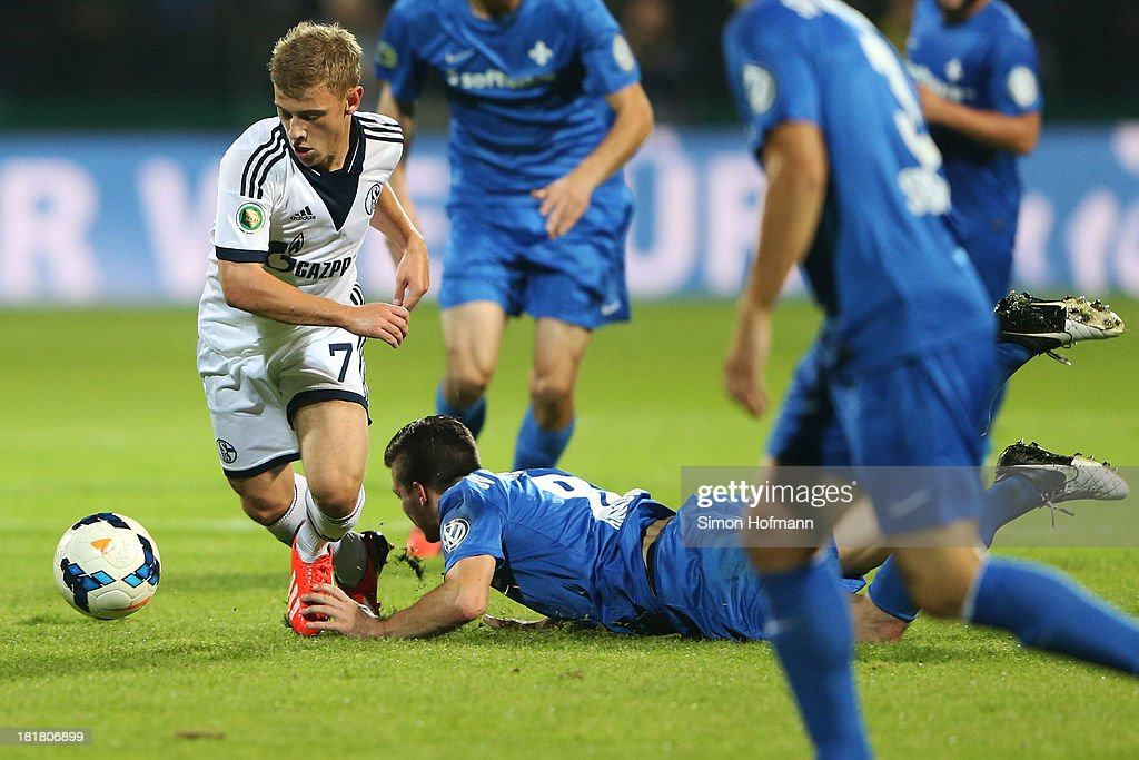 Max Meyer of Schalke is challenged by Jerome Gondorf of Darmstadt during the DFB Cup second round match between Darmstadt 98 and Schalke 04 at Stadion am Boellenfalltor on September 25, 2013 in Darmstadt, Germany.