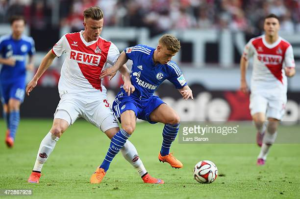Max Meyer of Schalke is challenged by Yannick Gerhardt of Koeln during the Bundesliga match between 1 FC Koeln and FC Schalke 04 at...