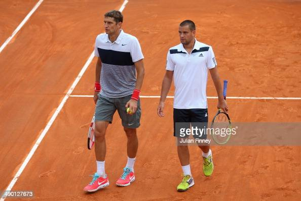 Max Mirnyi of Belarus and Mikhail Youzhny of Russia talk tactics in the doubles against Daniele Bracciali of Italy and Potito Starace of Italy during...
