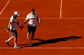 Max Mirnyi of Belarus taps hands with his partner Daniel Nestor of Canada during their men's doubles semifinal match against Daniele Bracciali of...