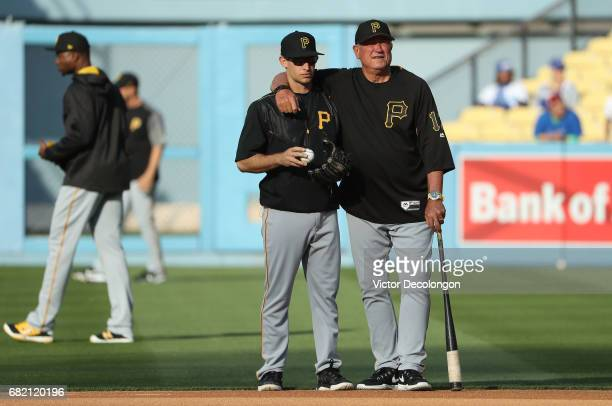 Max Moroff and manager Clint Hurdle of the Pittsburgh Pirates right watch batting practice from the infield prior to the MLB game against the Los...