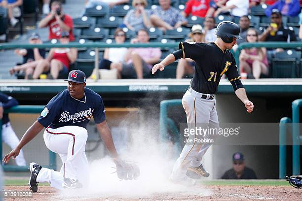 Max Moroff of the Pittsburgh Pirates slides safely at home plate after a wild pitch by Mauricio Cabrera of the Atlanta Braves in the eighth inning of...